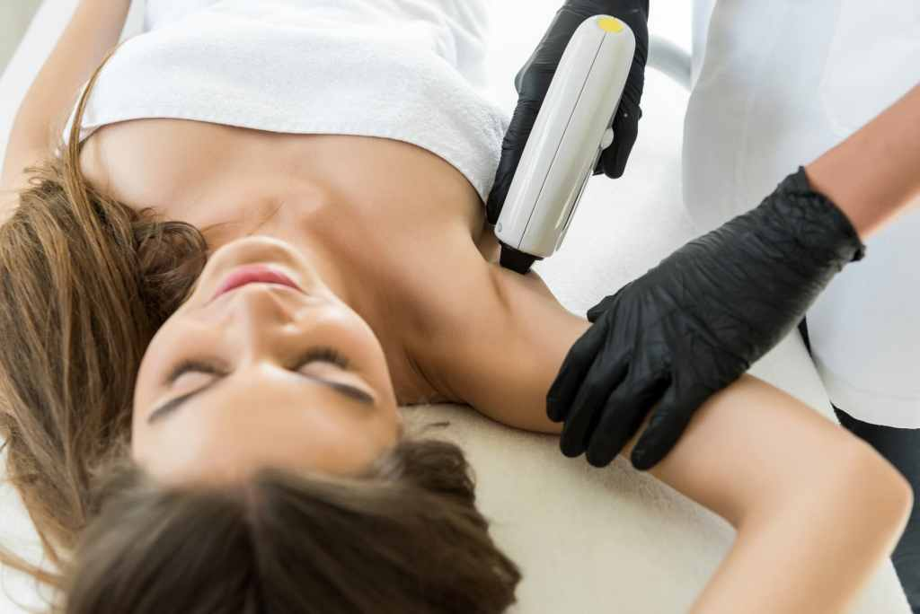 beautiful young woman having laser hair removal on armpits