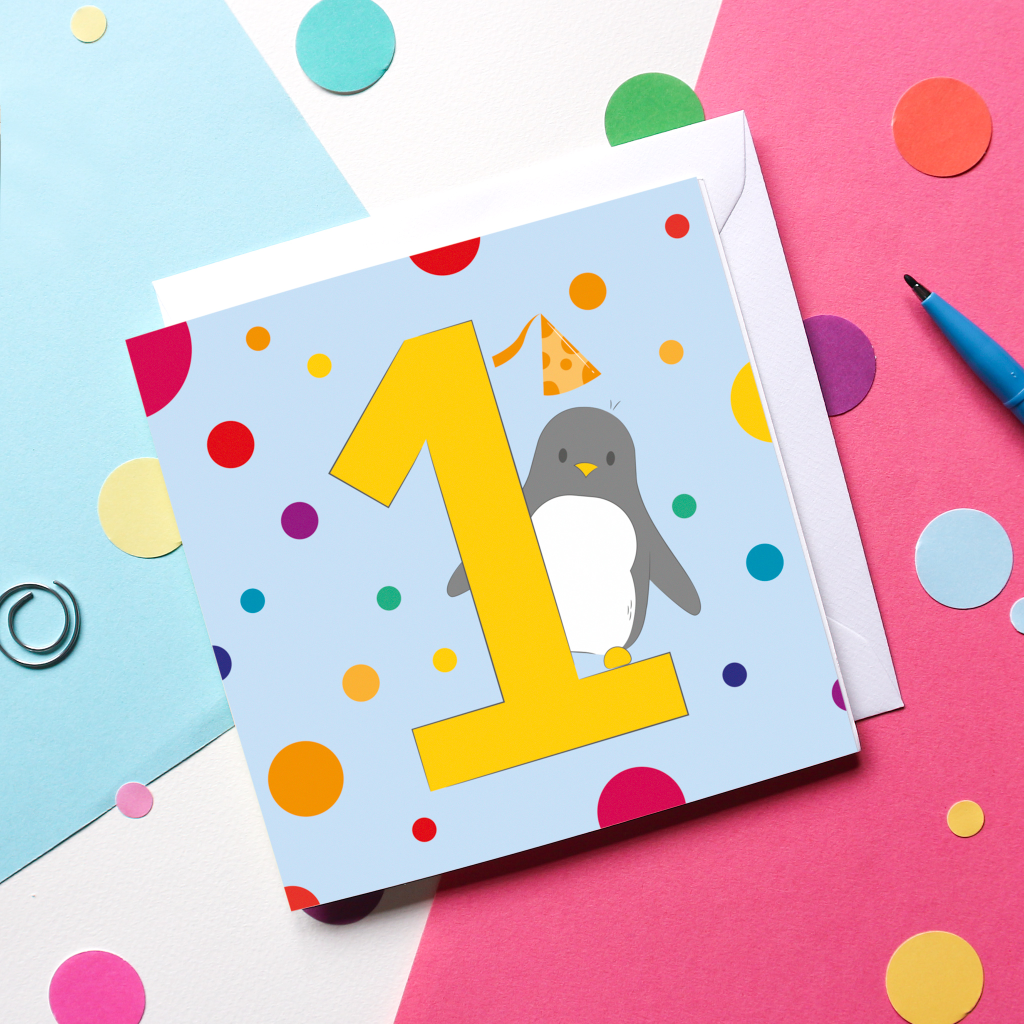 A Penguin-themed 1st Birthday Card on a colourful background surrounded by confetti and a pen.