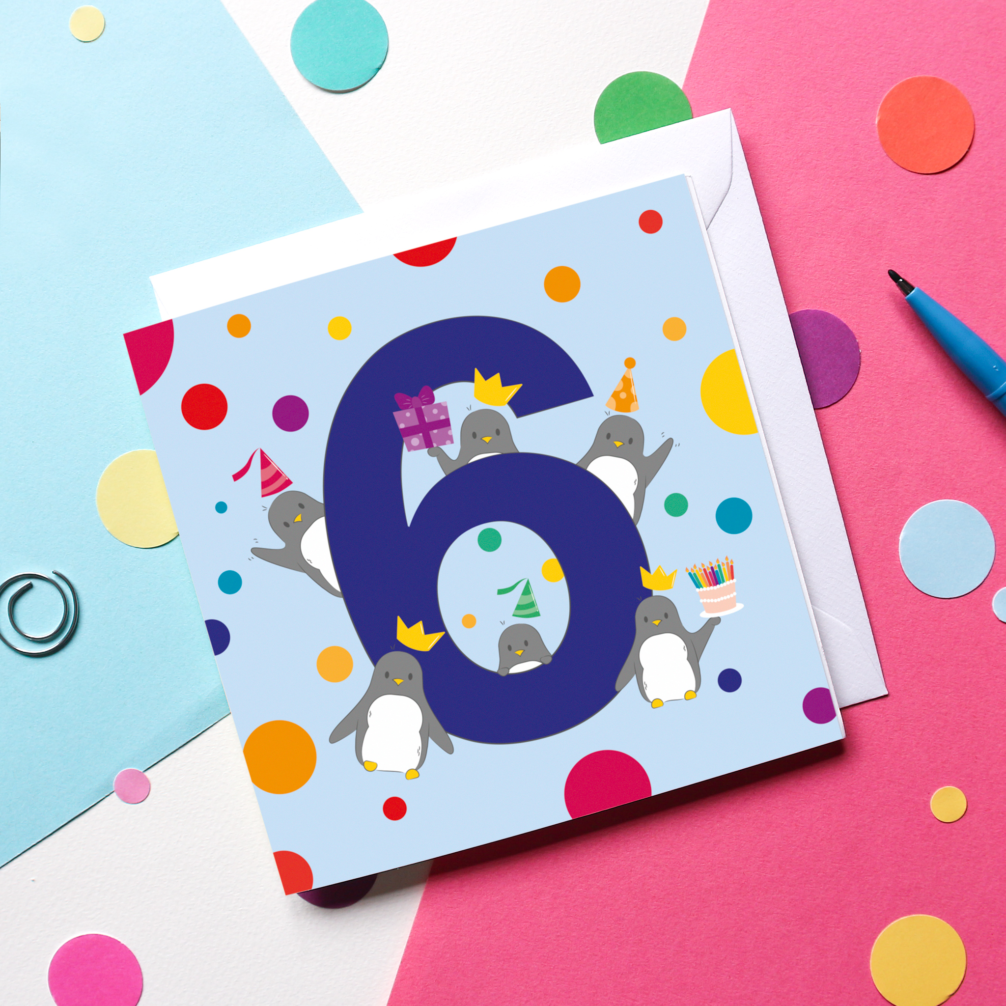 A Penguin-themed 6th Birthday Card on a colourful background surrounded by confetti and a pen.