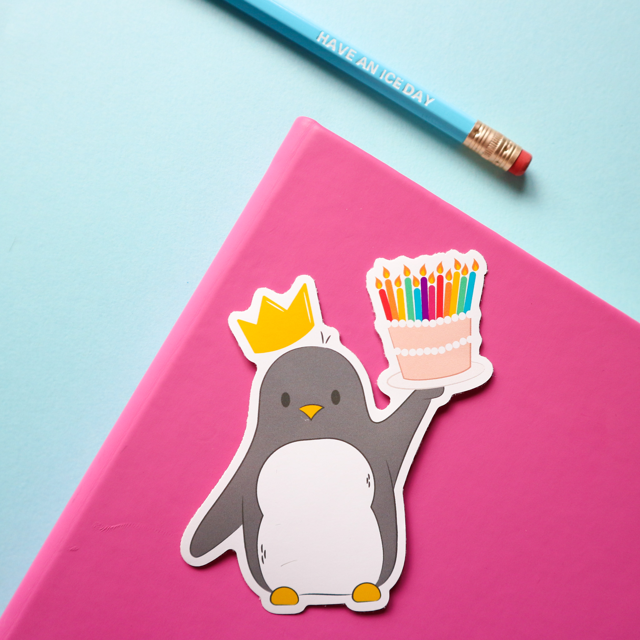 sticker design of penguin holding a birthday cake with lit, colourful candles on top and he's wearing a yellow birthday crown. The sticker is styled on a pink notebook with a blue pencil on a blue background.