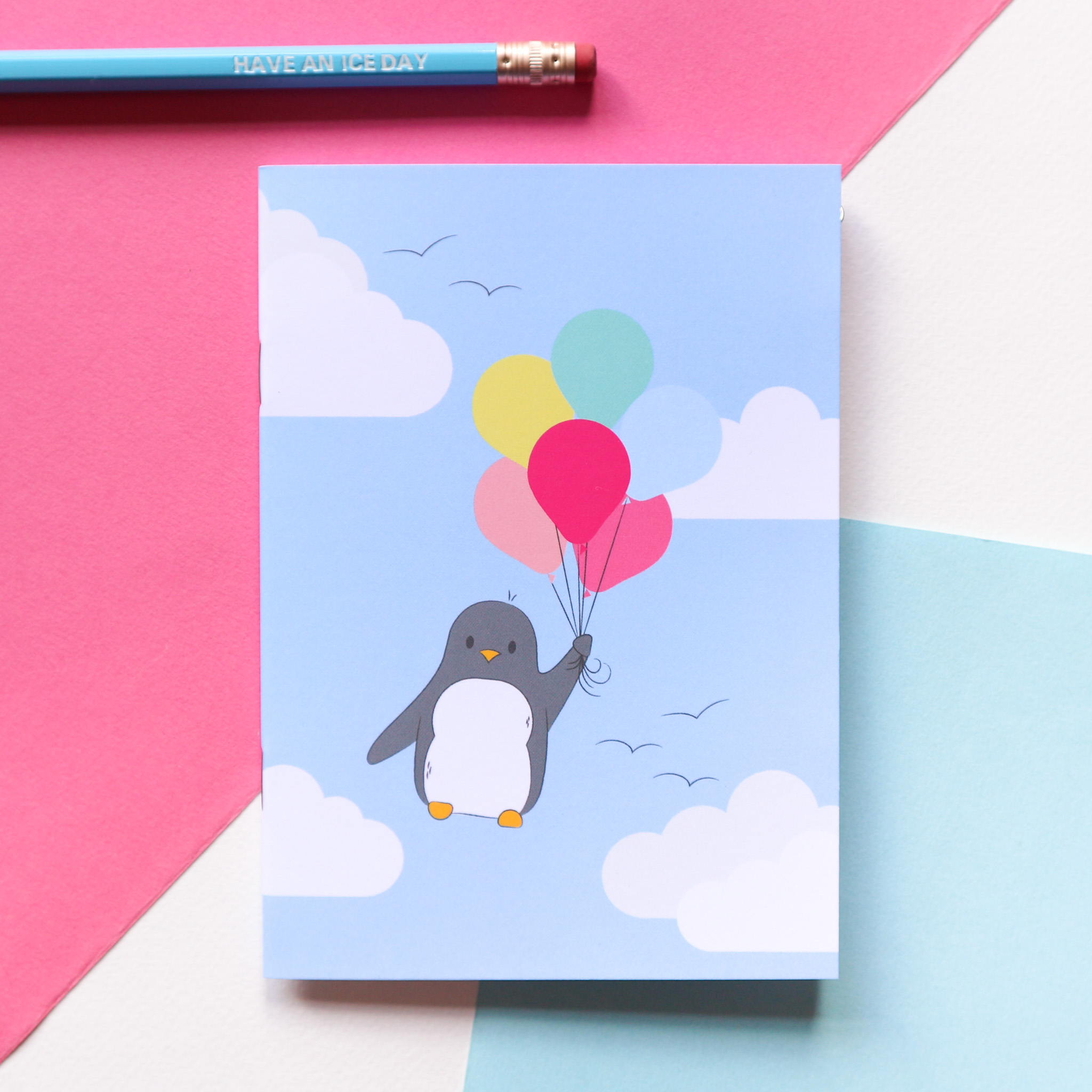 Penguin is floating away with a big bunch of balloons against a blue cloudy sky on this little notebook design. It is styled against a pink, blue and white background with a blue pencil.