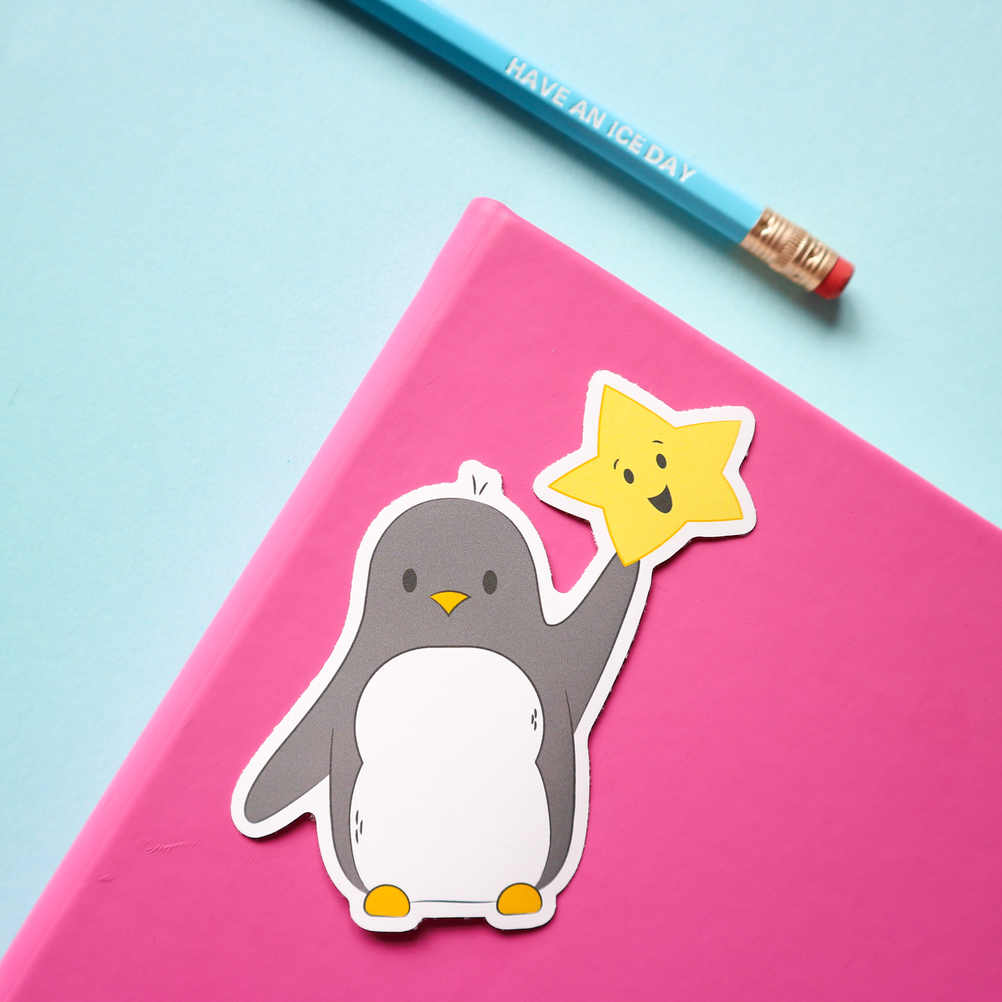 "sticker design of penguin holding a smiling star, against the background of a pink notebook, a pencil that say ""have an ice day"" all on a pale blue background. Pencil not included in this listing."