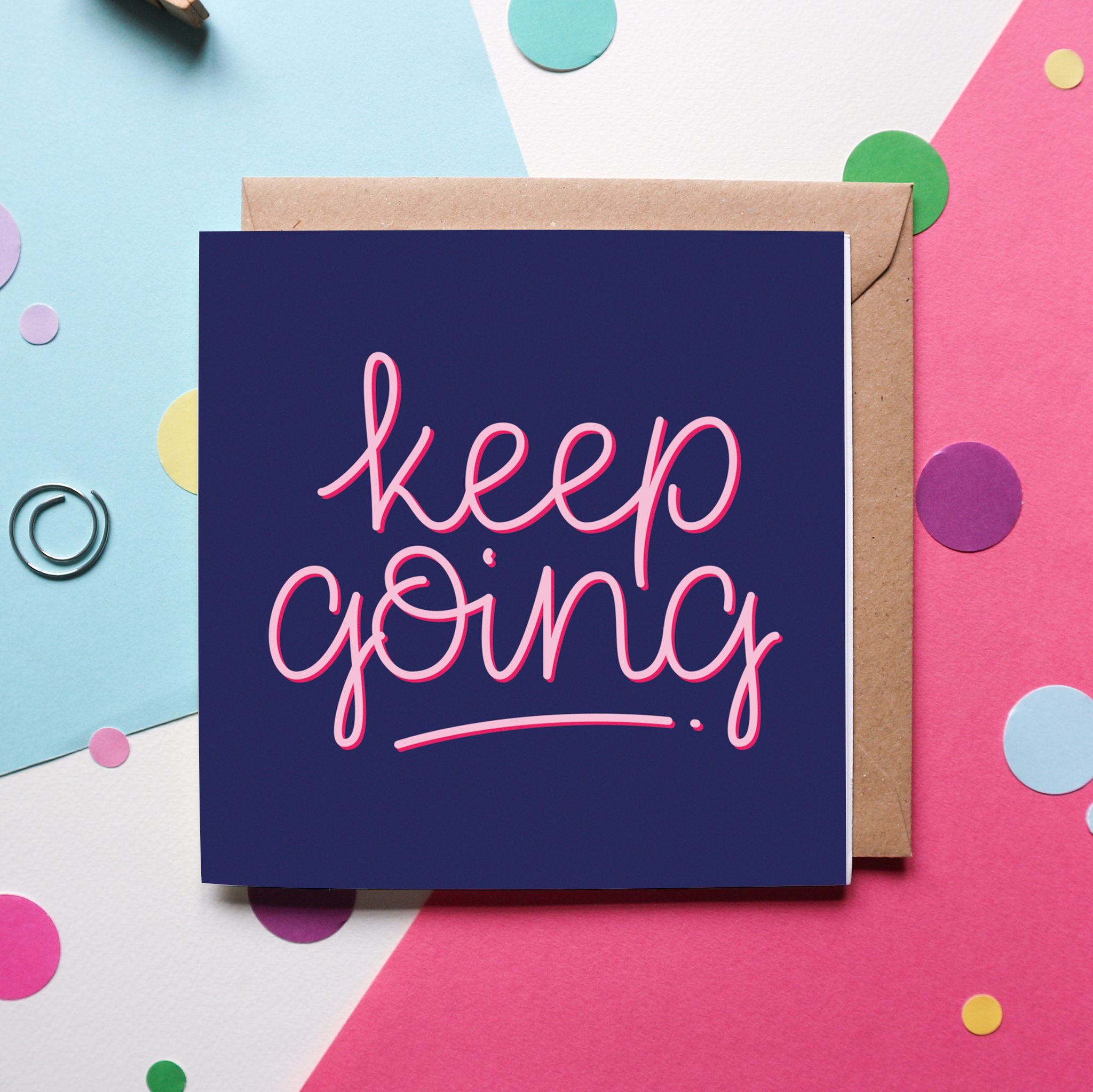 "A charming hand-lettered design that reads ""Keep Going"" in pink cursive, against a navy blue background on a greeting card. The greeting card sits against a brown, kraft envelope and against a pink and blue background with colourful confetti and paperclips."
