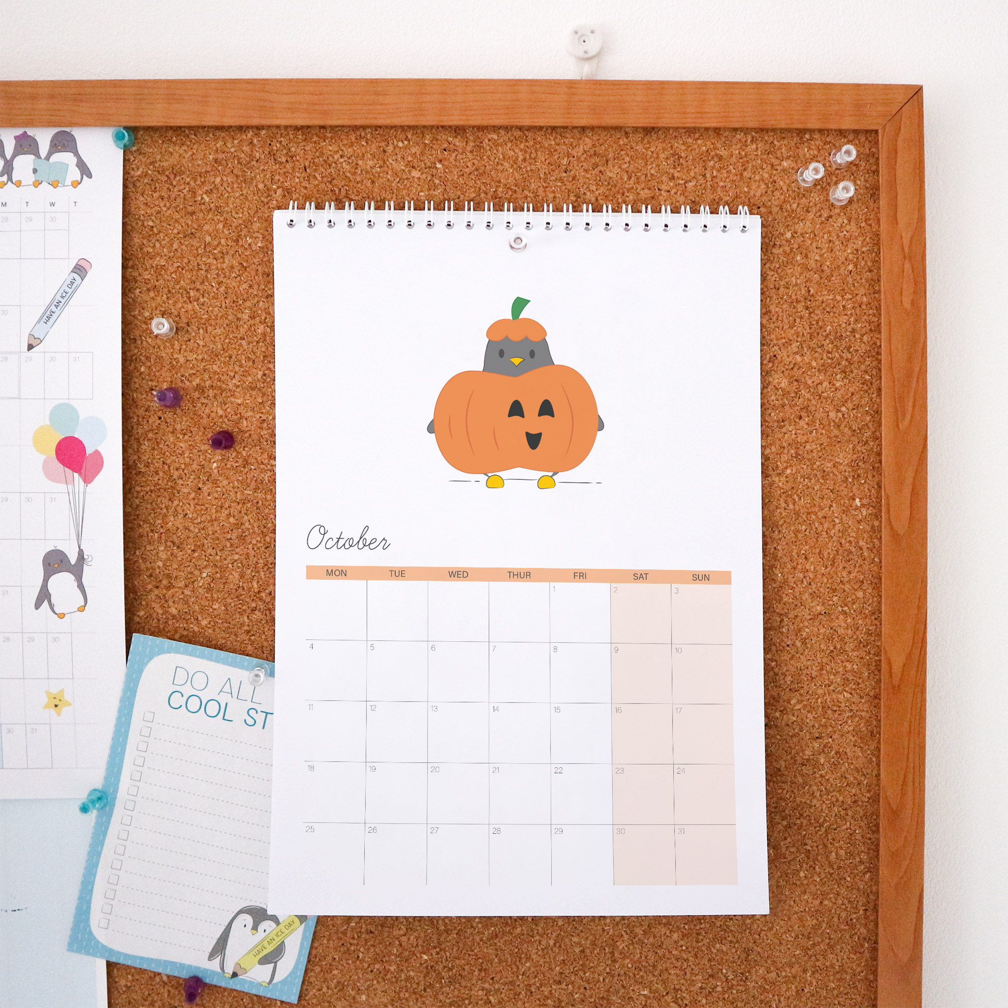 The October page of the calendar is an illustration of Penguin dressed as a pumpkin, he has a smiling orange pumpkin around his middle and is wearing an orange and green hat. This Calendar is wire bound A4 and is styled against a cork board background.