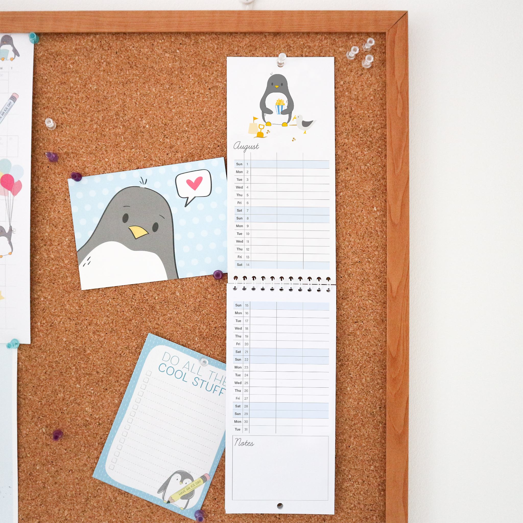 The August calendar page for 2021 is an illustration of penguin eating some chips at the beach and a naughty sea gull has stolen one! This Calendar is a wire bound tall calendar and is styled against a cork board background.