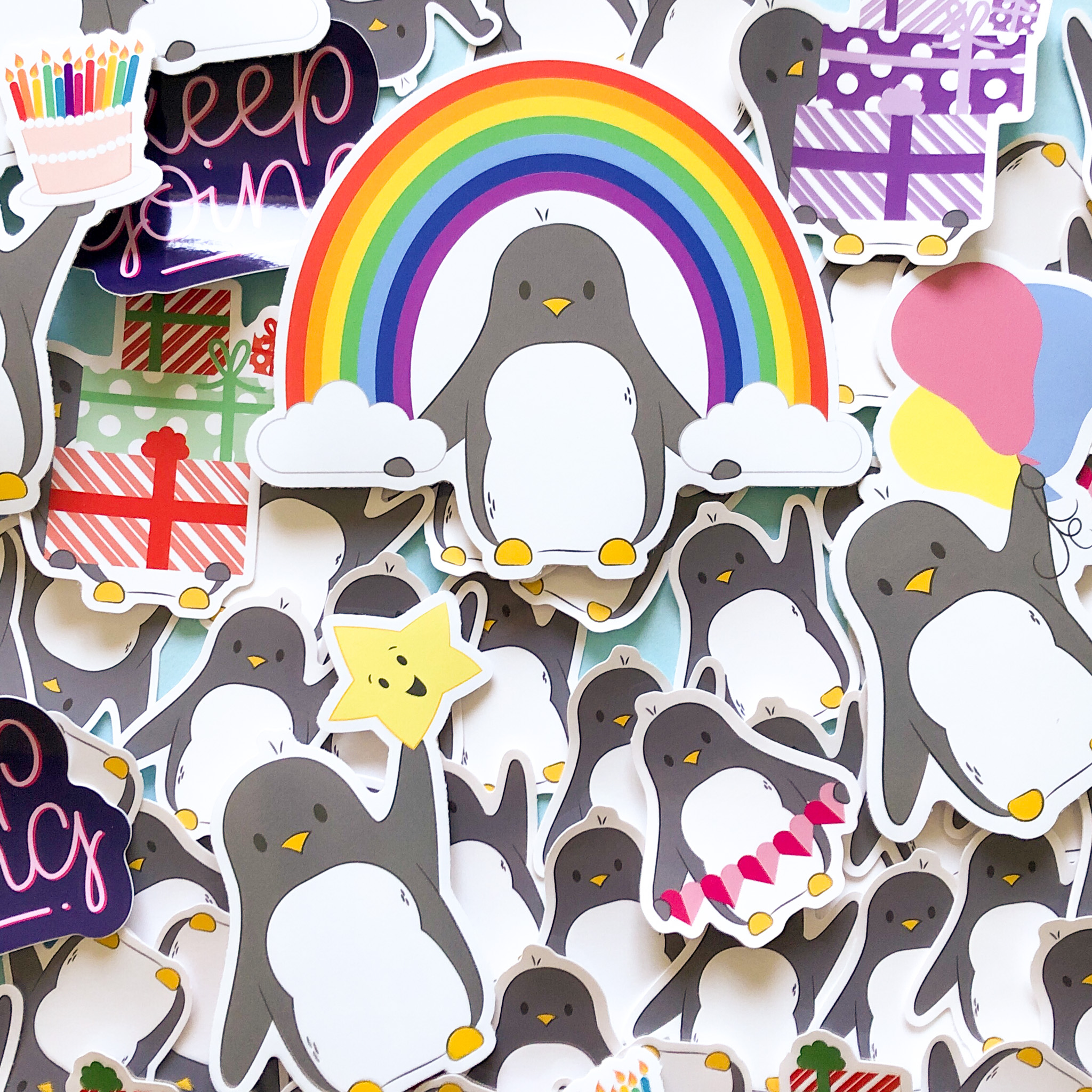 A selection of cute penguin stickers all overlapping on top of each other, they fill the frame.