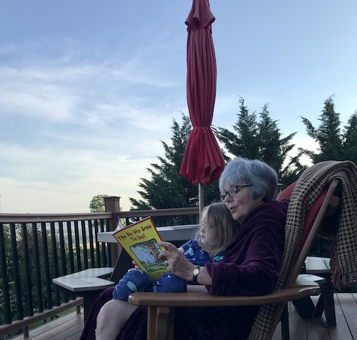 Reading as the sun comes up over the deck. Jammies and robe.