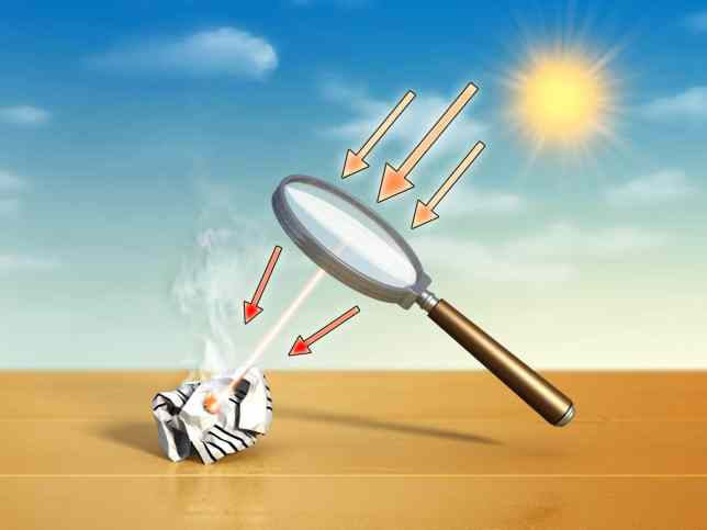 Magnifying glass starting a fire with concentrated sun rays.