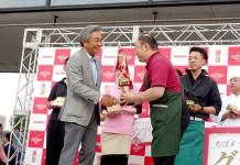 グランプリの宮本さんにトロフィーを授与する寺田直行社長㊧(カゴメ)