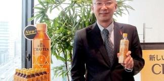 「紅茶花伝 クラフティー 贅沢しぼりオレンジティー」を手に山腰欣吾グループマネジャー