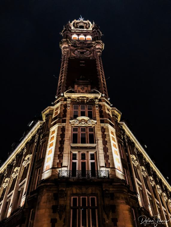 A night time photograph looking up at the belfry tower of the chamber of commerce building in lille