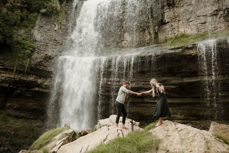 man and woman at waterfall