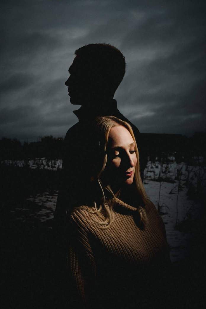 A man's silhouette appears against a cloudy winter sky. In front of his silhouette, a woman is light by a narrow beam of light. Black & Gold Photography uses unique lighting techniques to create wedding portraits using off-camera flash.