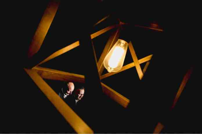 Two grooms' faces are highlighted between the angular bars of a modern light fixture. Black & Gold Photography made this unique wedding portrait using off-camera flash.