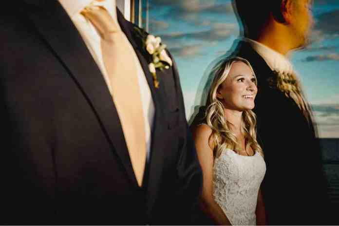A bride stands indoors facing a flash with a smile on her face. The groom stands closer to the camera, on the outdoor side of the window through which you can see the bride. His form and the blue sky are both reflected off the glass, surrounding the bride. Black & Gold Photography creates wedding portraits using off-camera flash.