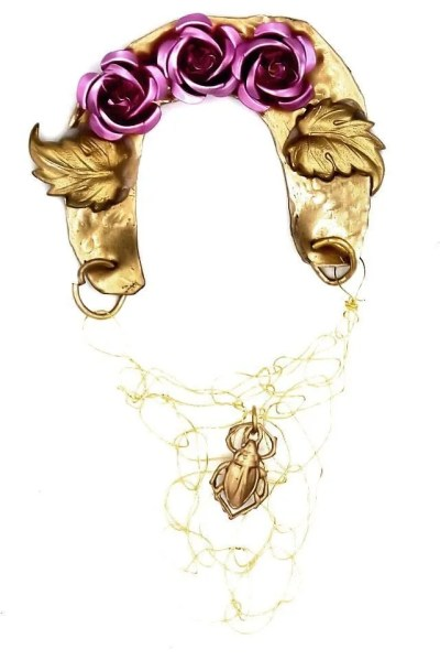 Brass earring that sits on top of ear features pink aluminum roses, brass leaves, a brass beetle sitting in crochet wire,