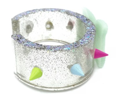 Hand poured resin cuff with rainbow spike accents and mint green bow in center.