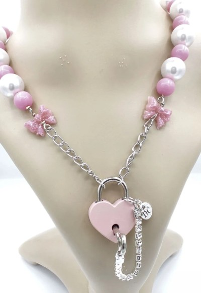 Front view of resin bows, pearls and pink beads with pink heart shaped padlock.