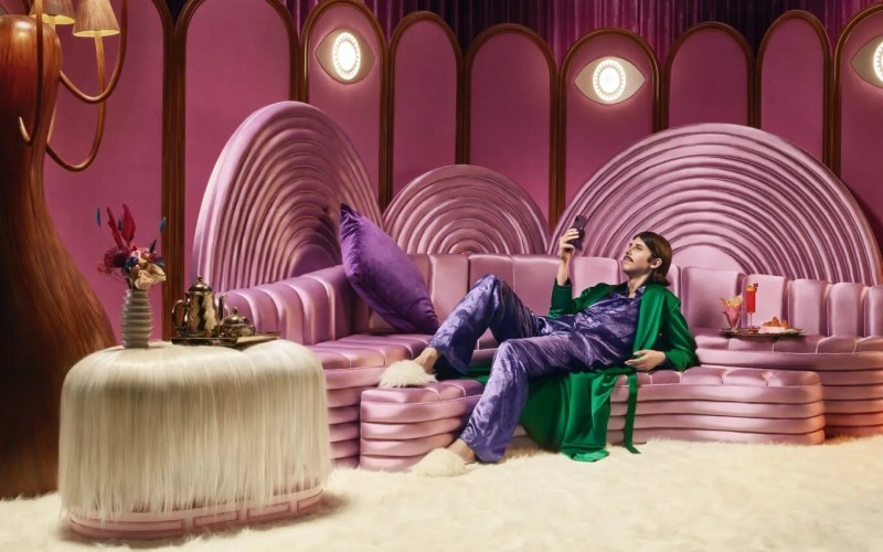 Man sitting on pink couch with phone in hand