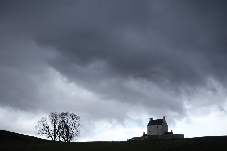 Corgarff Castle below ominous clouds