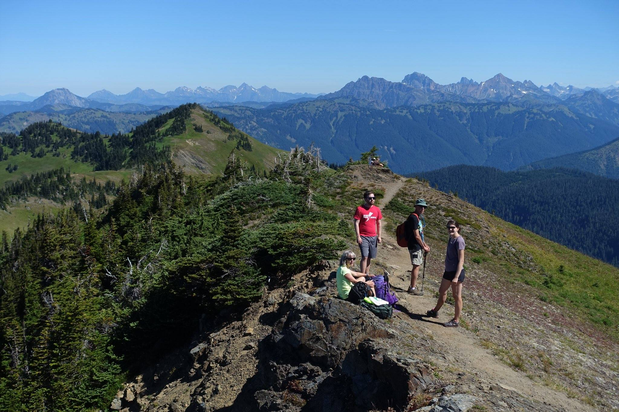 Four hikers stopped for lunch on a ridge with mountains in the background.