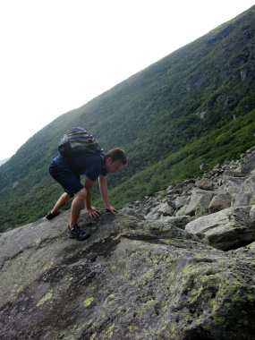 A hiker on a granite boulder in Huntington Ravine