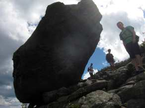 Three hikers pass below Glen Boulder