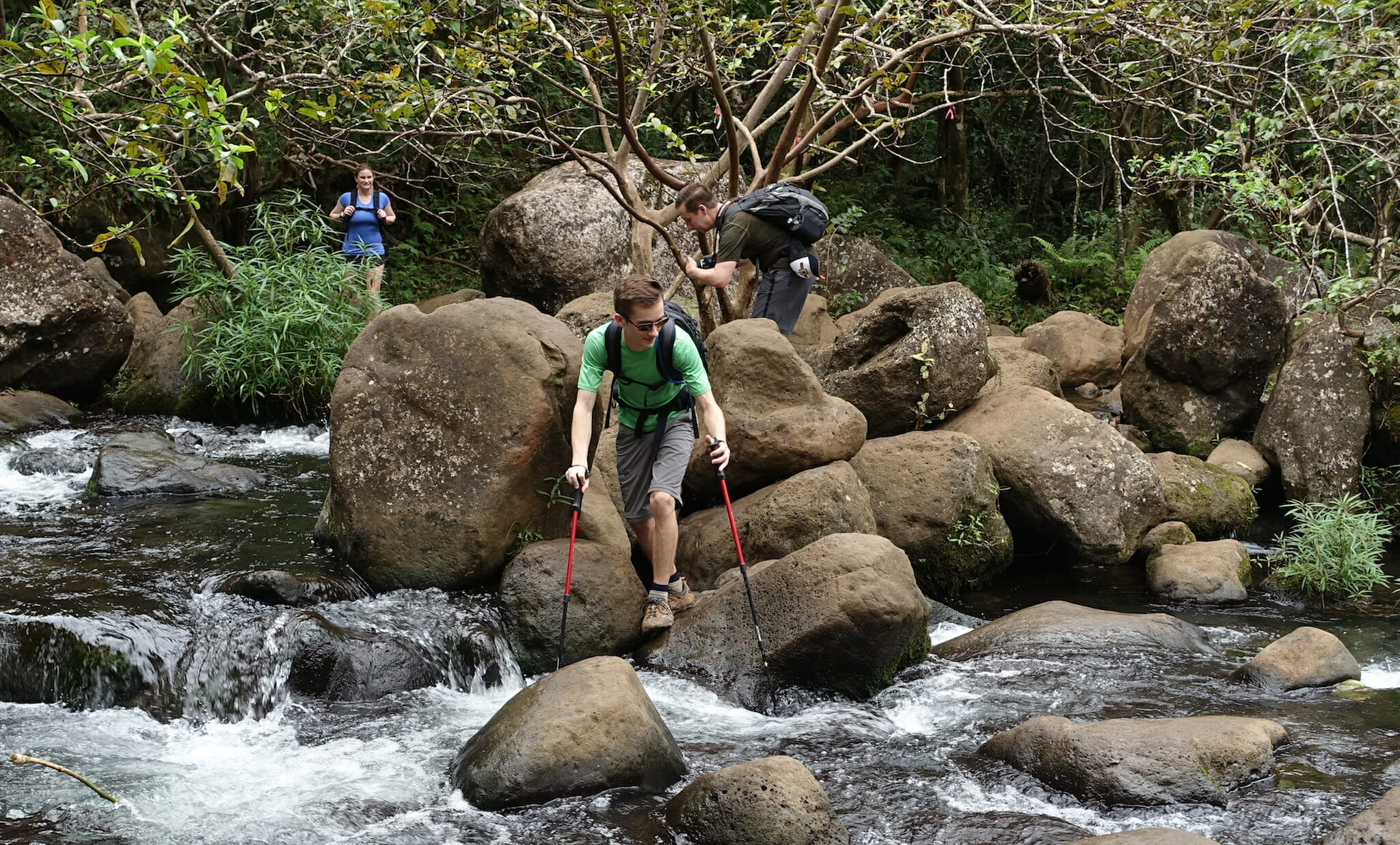 Kyle crossing Hanakapiai stream. Two other hikers in the background.