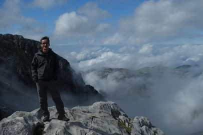 Kyle standing on rock with clouds and mountains in the background