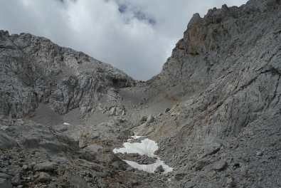 Snowfields and a trail through scree and boulders, leading up to a mountain pass