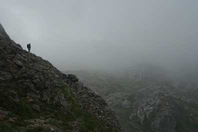 Kyle stands in the clouds/fog on a rocky slope above a valley with rocky outcroppings and green, rolling spots