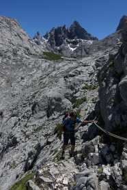 Kyle holding a cable along a narrow path, with mountain peaks in the background.