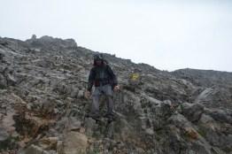 Kyle descends over broken rock in the rain, following a cable.