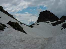 Hikers cross a snowfield on the TMB past Le Brevent