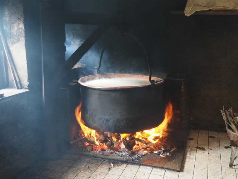 Large pot of Beaufort cheese on a wood fire
