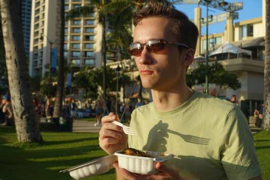 Kyle eating dinner along the beach in Waikiki