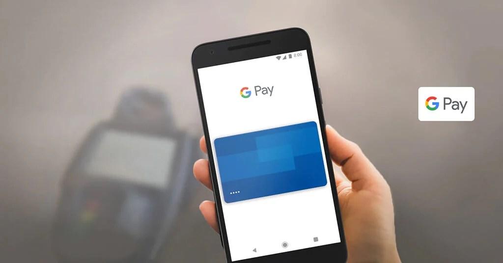 Um smartphone em primerio plano fazendo uma compra via Google Pay, com uma máquina de cartão atrás.
