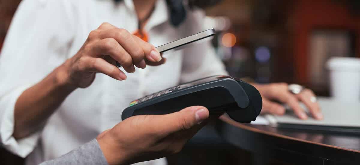 Uma mão segurando uma máquina de cartão, e outra pagando a compra com o smartphone.