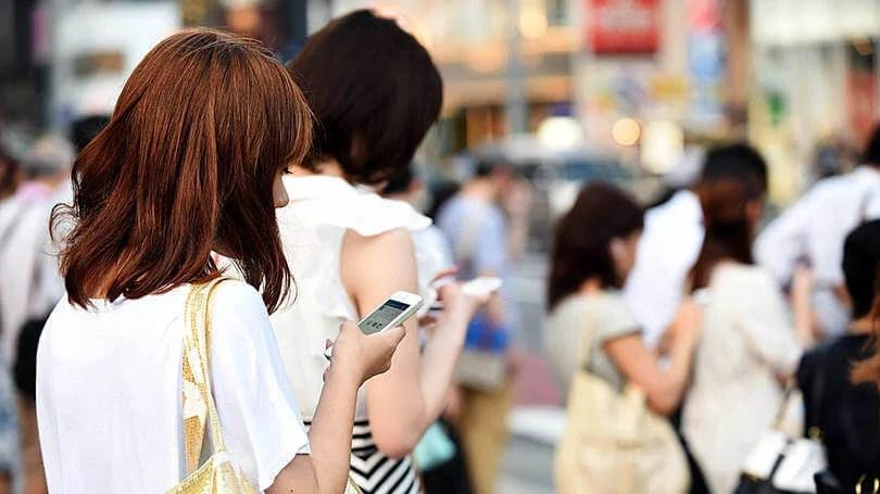 Pessoas na rua usando celular conectados via rede Wi-Fi.