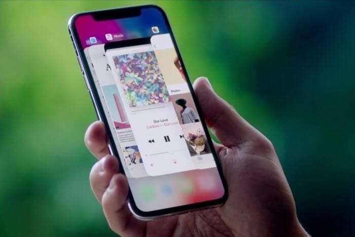 uma mão segurando um iPhone X