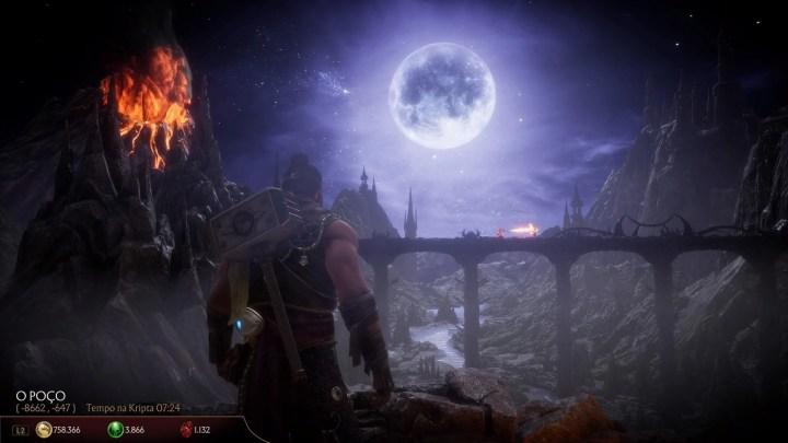 O personagem jogável da kripta, olhando para o cenário clássico the pit. Ao lado esquerdo, um vulcão escorrendo lava e dois personagens lutando sobre a ponte ao fundo.