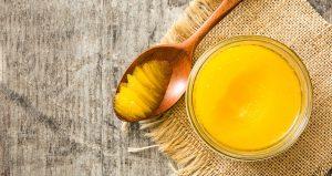 ghee-clarified-butter-jar-wooden-spoon-wooden-table