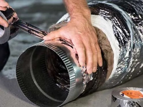 Hand applying silver tape to a section of HVAC vent