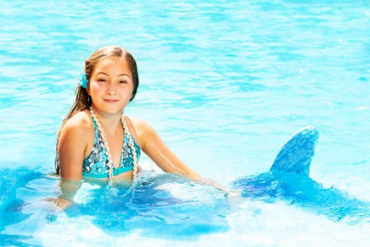 Retrato de cumpleañera en traje de sirena relajante en el agua azul de la piscina
