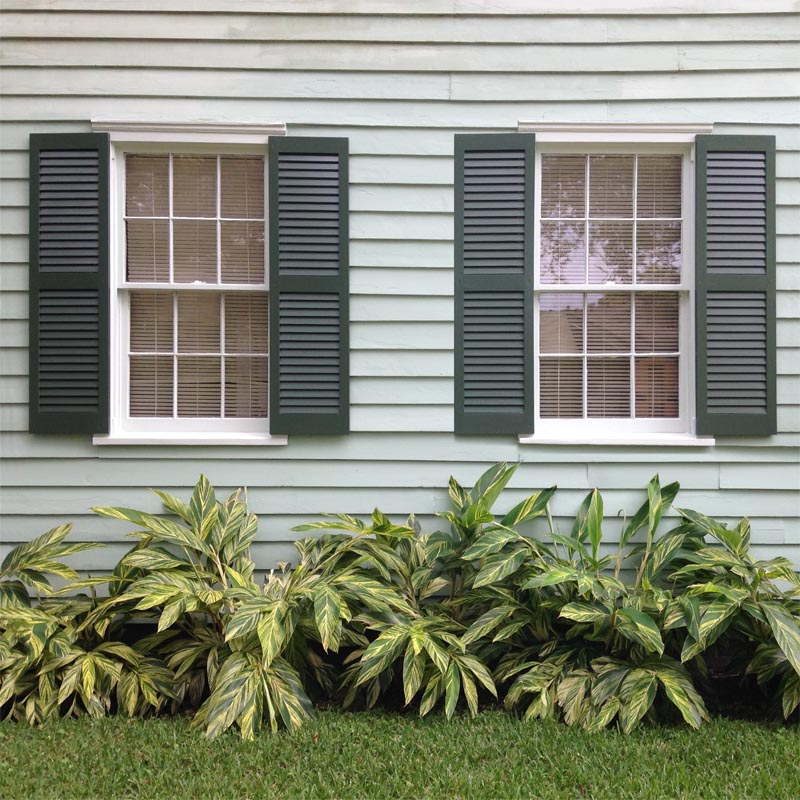 Louvered green pine shutters installed on outside windows.