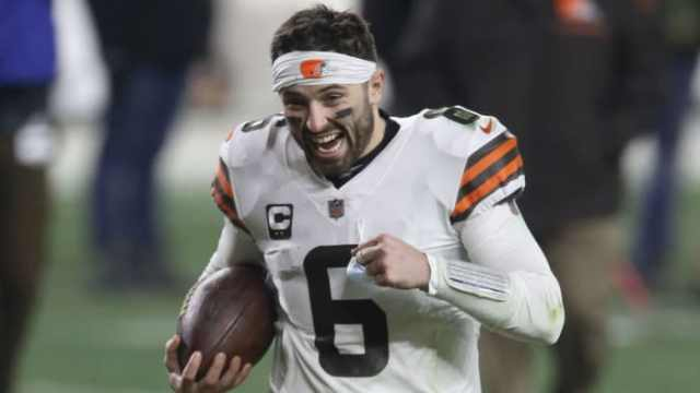 Baker Mayfield smiles as he runs off the field