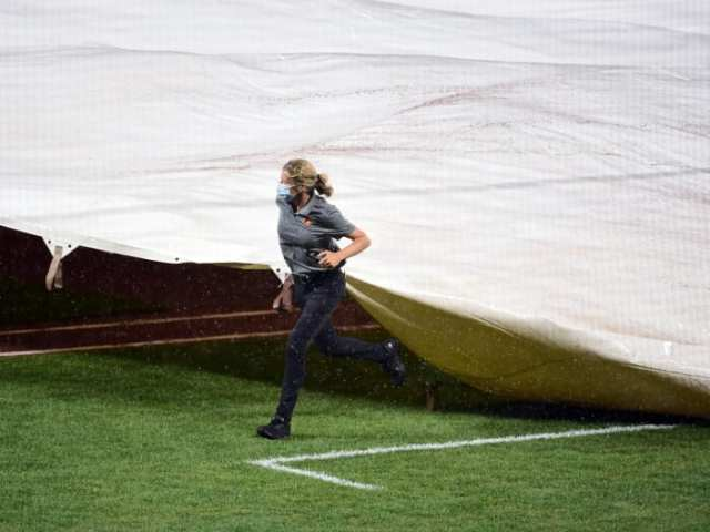 Jul 30, 2020; Baltimore, Maryland, USA; Baltimore Orioles head groundskeeper Nicole Sherry (center) covers the field with the tarp during a rain delay in a game against the New York Yankees at Oriole Park at Camden Yards.