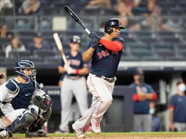 Jun 5, 2021; Bronx, New York, USA;  Boston Red Sox third baseman Rafael Devers (11) hits an RBI single during the sixth inning against the New York Yankees at Yankee Stadium. Mandatory Credit: