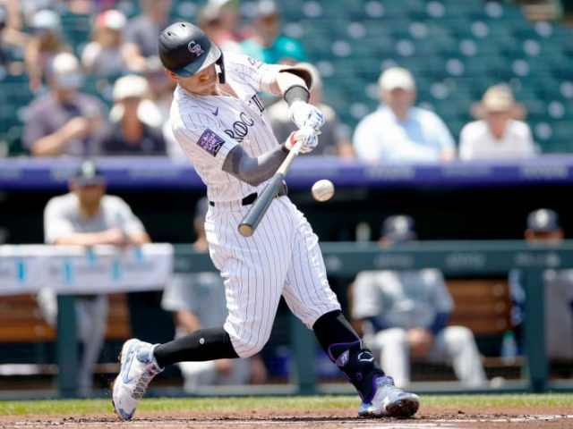 Jul 21, 2021; Denver, Colorado, USA; Colorado Rockies shortstop Trevor Story (27) hits a single in the first inning against the Seattle Mariners at Coors Field.