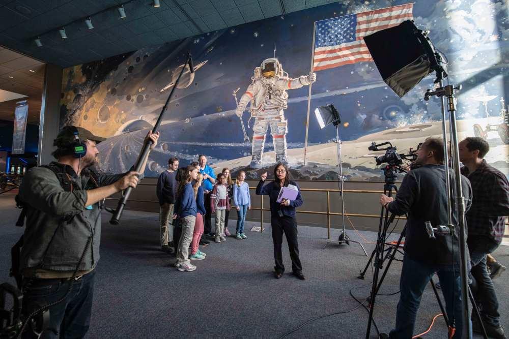 Groupe d'enfants regardent une femme filmée par des cameramen en face de la peinture murale représentant l'espace